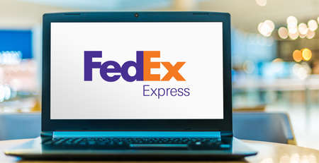 POZNAN, POL - AUG 8, 2020: Laptop computer displaying logo of FedEx Corporation, an American multinational delivery services company headquartered in Memphis, Tennessee