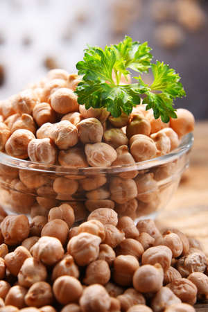 Composition with bowl of chickpeas on wooden table. 版權商用圖片