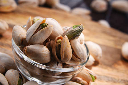 Composition with bowl of in shell pistachios. Delicacies