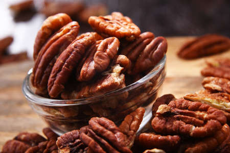 Composition with a bowl of shelled pecan nuts. Delicacies