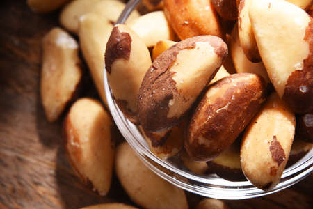 Composition with a bowl of shelled brazil nuts. Delicacies