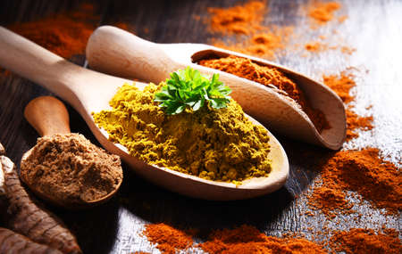 Composition with spices on wooden kitchen table.