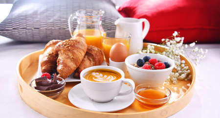 A tray with breakfast on a bed in a hotel room. Imagens