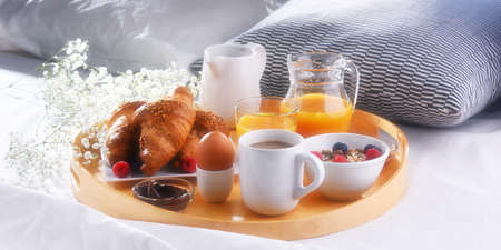A tray with breakfast on a bed in a hotel room. Standard-Bild
