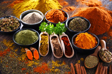 Variety of spices on wooden kitchen table.