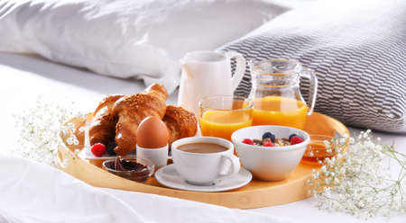 A tray with breakfast on a bed in a hotel room. 写真素材
