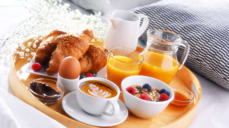 A tray with breakfast on a bed in a hotel room. 版權商用圖片
