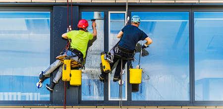 Two men cleaning windows on an office building Standard-Bild