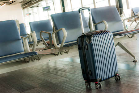 Small plastic travel suitcase in the airport hall. 写真素材
