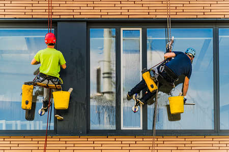 Two men cleaning windows on an office building 写真素材
