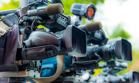 Professional tv cameras on tripods recording social event on the street