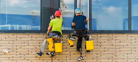 Two men cleaning windows on an office building 新聞圖片