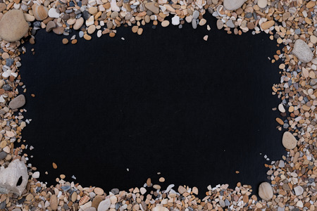 Small sea stones and shells, on a black background, with a free space on the center under the text, title, ad, menu or picture.