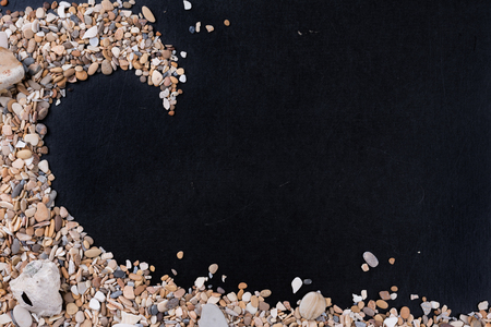 Small sea stones and shells on the left corner, on a black background, with a free space under the text, title, ad, menu or picture.