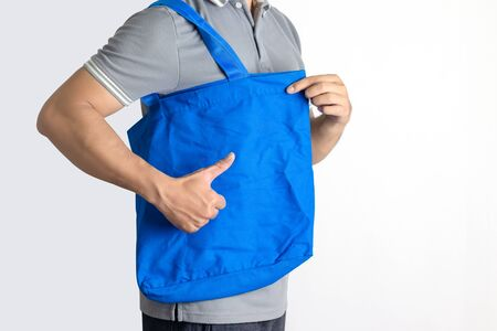 Man is holding blank canvas tote bag. Eco shopping bag.