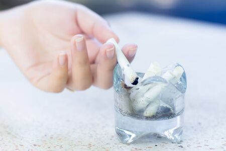 Hand of women drop cigarettes butts in glass ashtray. Stok Fotoğraf