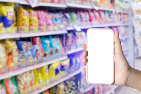 Hand holding mobile phone with supermarket background, online shopping concept.
