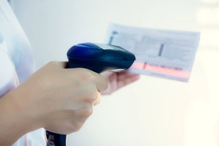 closeup of hand holding bar code scanner and scanning code on Invoice