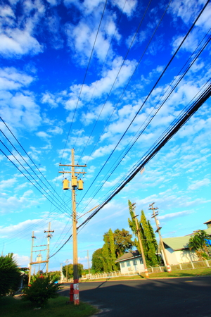 isolator insulator: Transformers of an electrical post with powerlines against bright blue sky