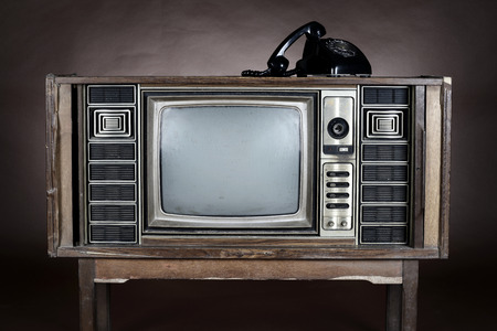 television set: Old  telephone put on an vintage television on brown background.