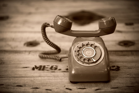 Old black phone with dust and scratches on wooden retro floor