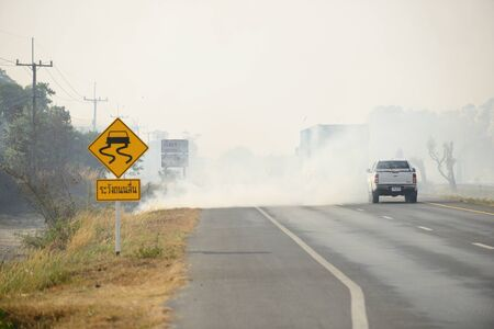 Burning dry grass along the road, causing a hazard. Stok Fotoğraf