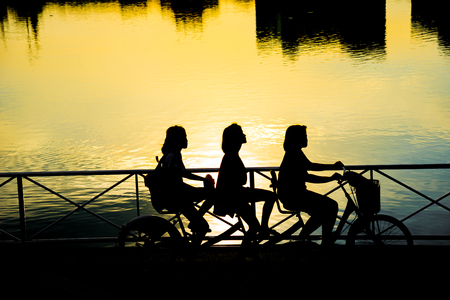 silhouette people cycling in the park with colorful sunset