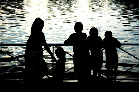 mujer mirando el horizonte: Siluetas de personas en un lago al atardecer