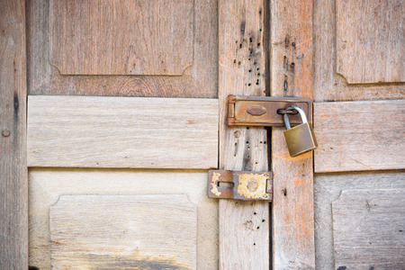 circumspect: The old padlock on wooden vintage style door.