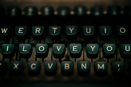 screenwriter: close up of keys of vintage typewriter with text I LOVE YOU on keys .Toned image.