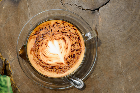 under heart: A cup of coffee with heart pattern on wooden background under the morning sunlight