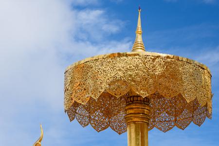 tiered: Gold tiered umbrella under blue sky
