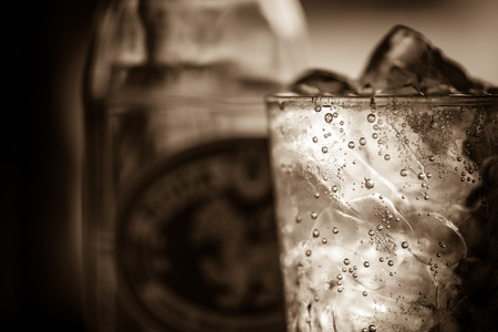 film noir: A glass of soda water with ice in sepia tone.Toned image,soft focus,film noir style.
