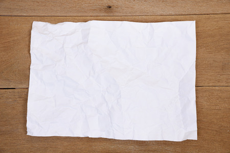 crumpled: Crumpled paper sheet on a wooden background Stock Photo
