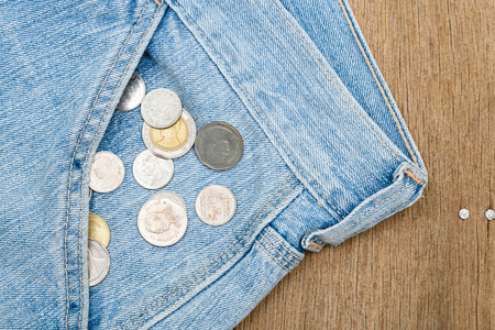 falling out: Coins falling out of jeans pocket on wooden background