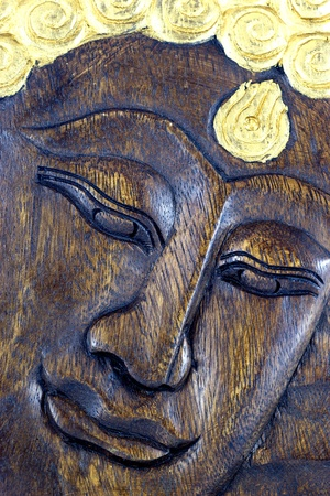 Face of Lord Buddha, native Thai style wood carving photo