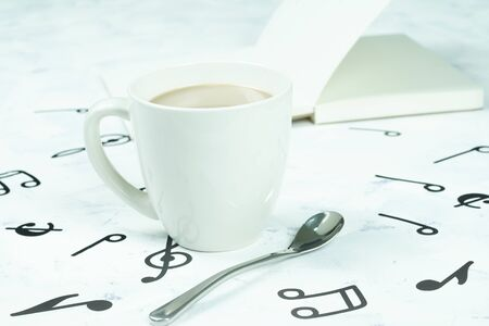 Coffee cup and book placed on the floor, musical note pattern Stok Fotoğraf