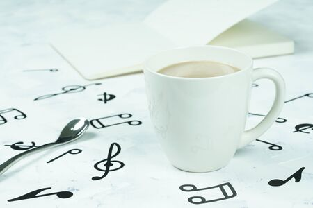 Coffee cup and notebook placed on the floor, musical note pattern Stok Fotoğraf
