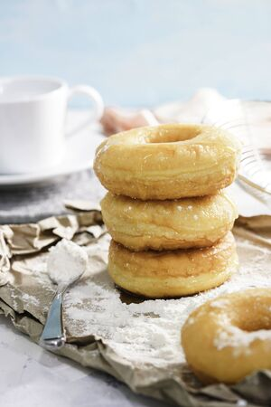 Homemade fried donuts or cronuts in stack with sugar standing on crumpled paper over white wooden concrete table. Stok Fotoğraf