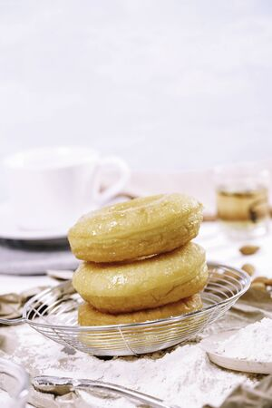 Homemade fried donuts or cronuts in stack with sugar standing on crumpled paper over white wooden concrete table, leaving space for text