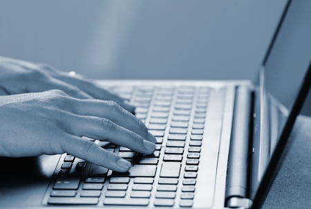 inputting: Hands typing on the keyboard of a laptop Stock Photo