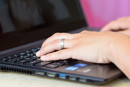 inputting: Close-up of female hands typing on keyboard