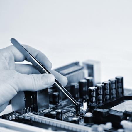 componentes: Mano con las pinzas sobre placa con componentes