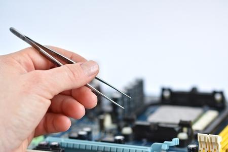 tweezers: Mano con las pinzas sobre placa con componentes