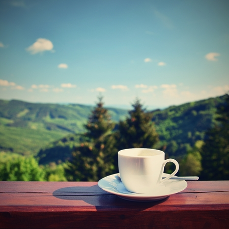 Morning cup of coffee with a beautiful mountain landscape background. White cup and saucer and espresso on a wooden table. Standard-Bild