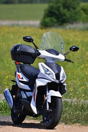 Bella piccolo scooter bianco in natura. Offuscata sfondo colorato. L'ideale mezzo di trasporto in città e in campagna. Trasporto.