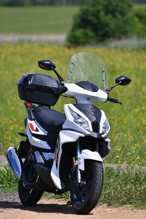 Beautiful white little scooter in nature. Blurred colorful background. The ideal means of transport into the city and into the countryside. Transport.