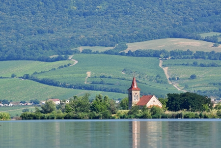 The island with the old church in the middle of the lake. Landscape under Palava. Czech Republic - South Moravian Region wine region. Water tank - New Mills - Pasohlavky. Stock Photo