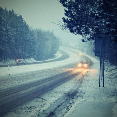 winter weather: Cars in the fog. Bad winter weather and dangerous automobile traffic on the road. Light vehicles in fog.