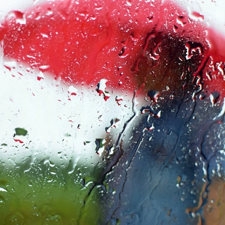 A man under an umbrella in the rain. Drops with a blurred background.